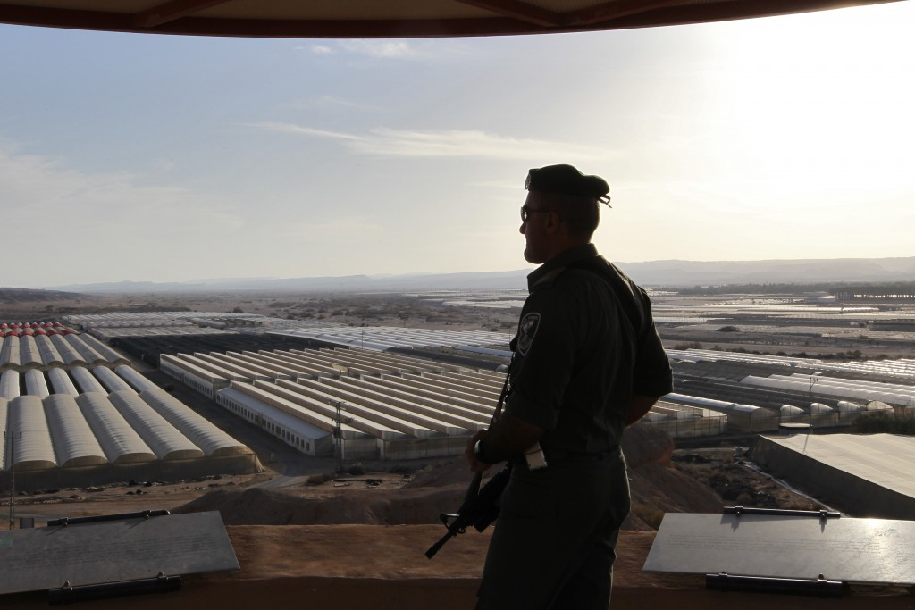 A border policeman looks at greenhouses from his watch tower near the Jordan border. (Nati Shohat/Flash90)