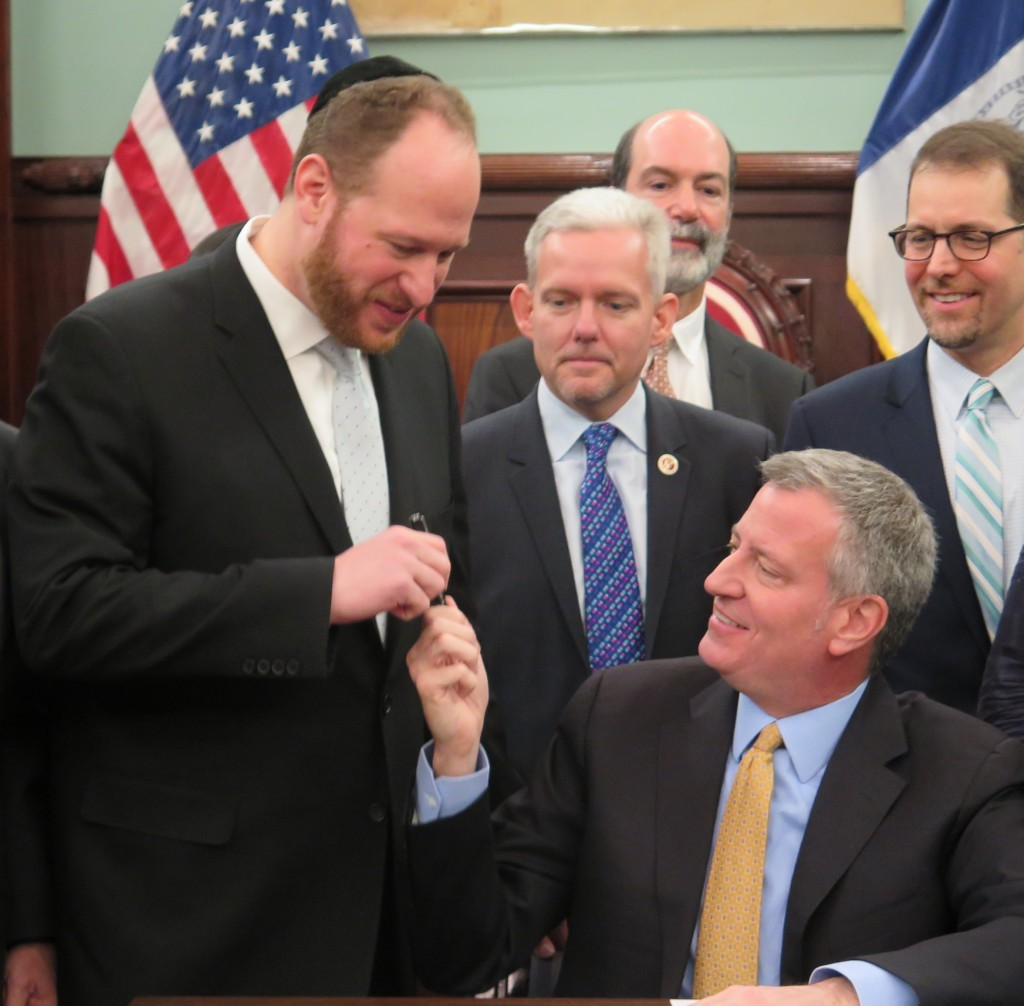Mayor Bill de Blasio on Tuesday hands Councilman David Greenfield the pen he used to sign into law a $19.8 million measure providing for the first time security guards for yeshivos. (William Alatriste/NYC Council)