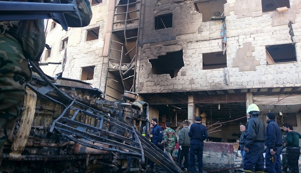Residents and soldiers loyal to Syria's President Bashar al-Assad inspect damage after the suicide attack in Sayeda Zeinab, a district of southern Damascus, Syria, on Sunday. (Reuters/Stringer)