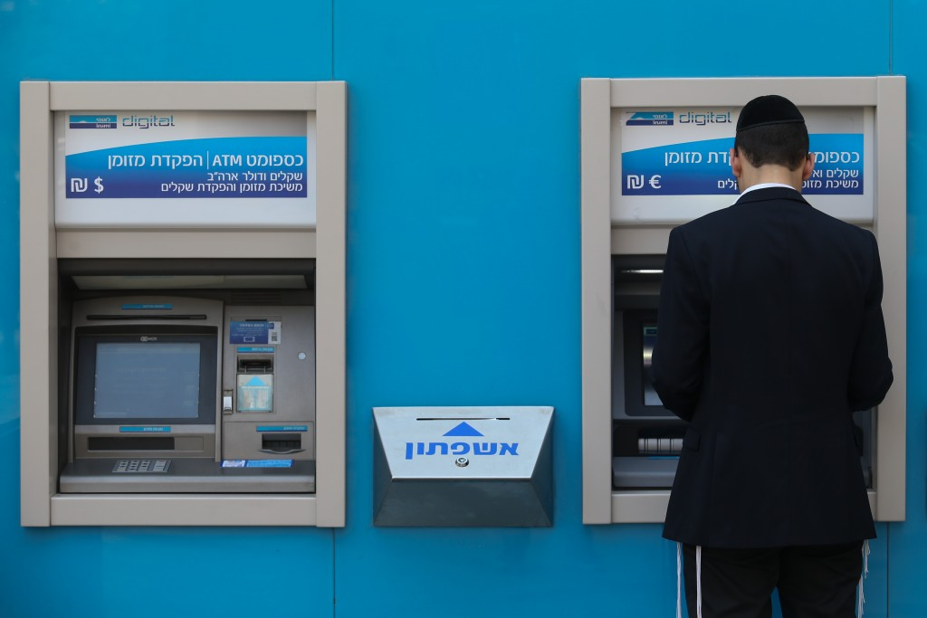 A Jewish man cashes out money from an ATM machine in Yerushalayim. (Nati Shohat/Flash90)