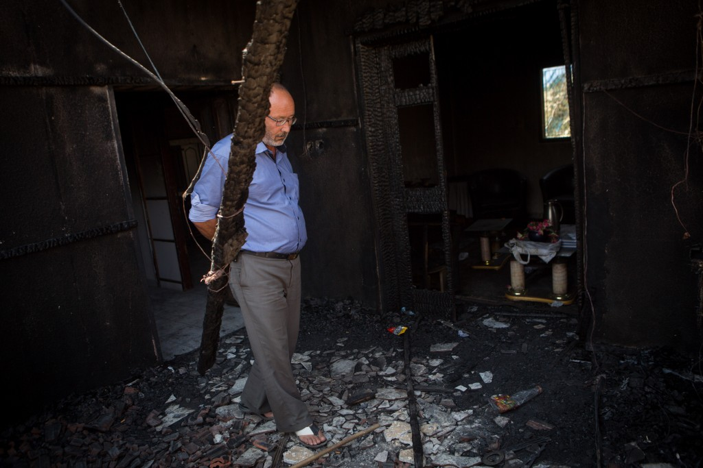 A Palestinian man looks at the damage in the Dawabshe family's home in the West Bank village of Duma, on August 06, 2015, after it was set on fire. Photo by Miriam Alster/FLASH90