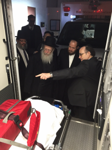 Minister Rabbi Litzman taking a look at one of Hatzolah's ambulances with Central Hatzolah board members. (Hatzolah)