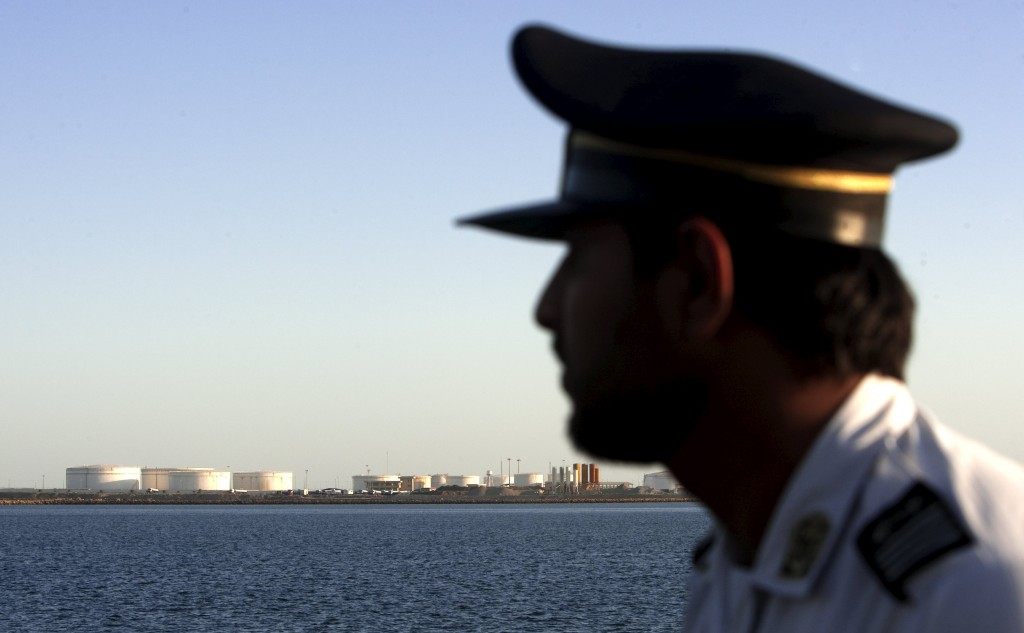 EDITORS' NOTE: Reuters and other foreign media are subject to Iranian restrictions on leaving the office to report, film or take pictures in Tehran.A security personnel looks on at oil docks at the port of Kalantari in the city of Chabahar, 300km (186 miles) east of the Strait of Hormuz in this January 17, 2012 file photo. As Iran fully returns to oil markets after the lifting of sanctions, Tehran is working to re-establish its national oil company as the sole marketer of Iranian crude and steering customers clear of middlemen. REUTERS/Raheb Homavandi/Files