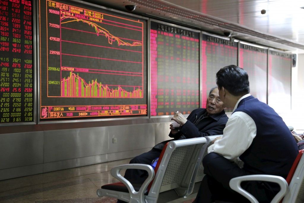 Investors chat in front of an electronic board showing stock information at a brokerage house in Beijing, China, October 30, 2015. China stocks closed mixed on Friday as food and beverage shares gained on announced reforms to the country's one-child policy rule, but manufacturing lagged. REUTERS/Li Sanxian CHINA OUT. NO COMMERCIAL OR EDITORIAL SALES IN CHINA (Newscom TagID: rtrlseven416944.jpg) [Photo via Newscom]
