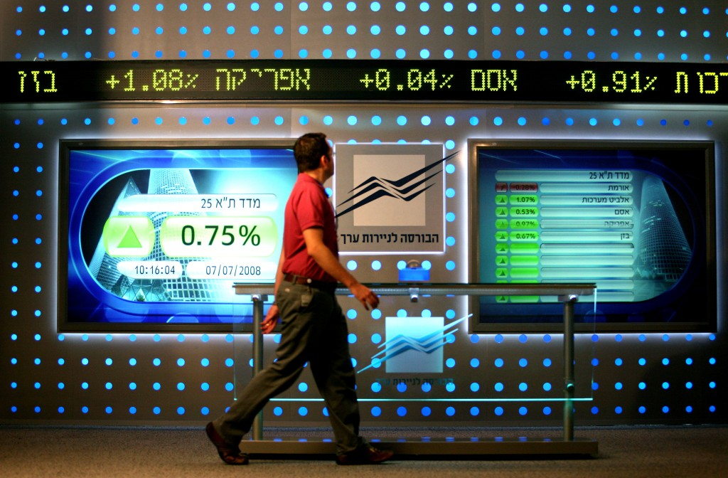 A man walks past a board showing stock fluctuations at the Tel Aviv stock exchange. Photo by Moshe Shai/FLASH90