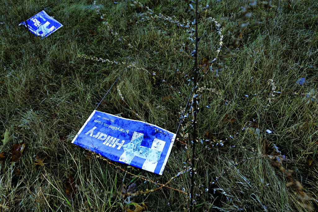 """DERRY, NH - FEBRUARY 02: Campaign signs for Democratic presidential candidate Hillary Clinton lie blown over near the roadside February 2, 2016 in Derry, New Hampshire. After Monday's Iowa caucuses, all the presidential candidates are now turning their sites on New Hampshire and the """"First in the Nation"""" primary. (Photo by Chip Somodevilla/Getty Images)"""