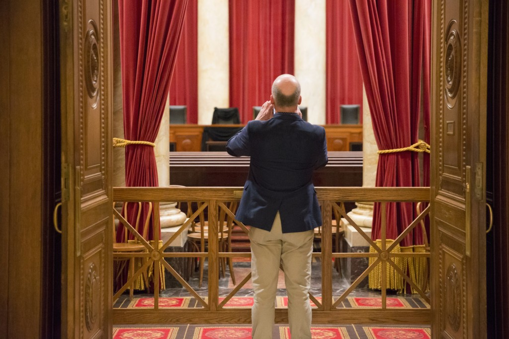 A Supreme Court visitor takes a photo of Supreme Court Justice Antonin Scalia's courtroom chair draped in black to mark his death, part of a tradition that dates to the 19th century, in Washington, Tuesday, Feb. 16, 2016, at the court in Washington. Scalia died Saturday at age 79. He joined the court in 1986 and was its longest-serving justice. (AP Photo/J. Scott Applewhite)