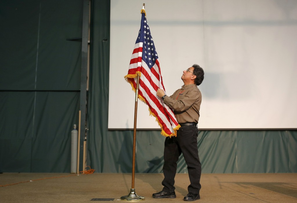 A worker adjusts an American flag at the Republican caucus at the 7 Flags Event Center in Clive, Iowa February 1, 2016. (Aaron P. Bernstein/Reuters)