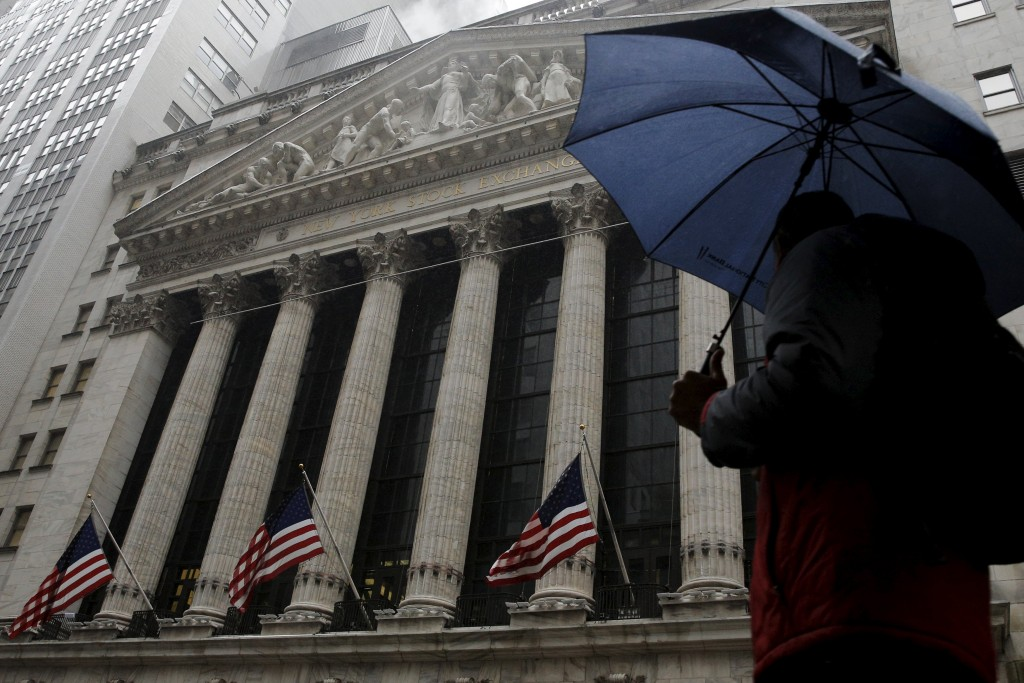 A man passes by the New York Stock Exchange during a rain storm in New York February 24, 2016. (Brendan McDermid/Reuters)