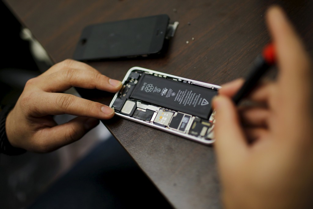 A worker tries to repair an iPhone in a repair store in New York, in this February 17, 2016 file photo. Apple Inc will likely seek to invoke the United States' protections of free speech as one of its key legal arguments in trying to block an order to help unlock the encrypted iPhone of one of the San Bernardino shooters, lawyers with expertise in the subject said this week. Picture taken February 17, 2016. REUTERS/Eduardo Munoz/Files