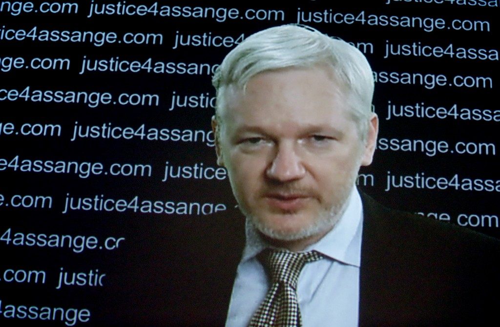 Julian Assange is seen on a screen as he addresses the media from the Ecuadorian embassy in London. (AP Photo/Frank Augstein)