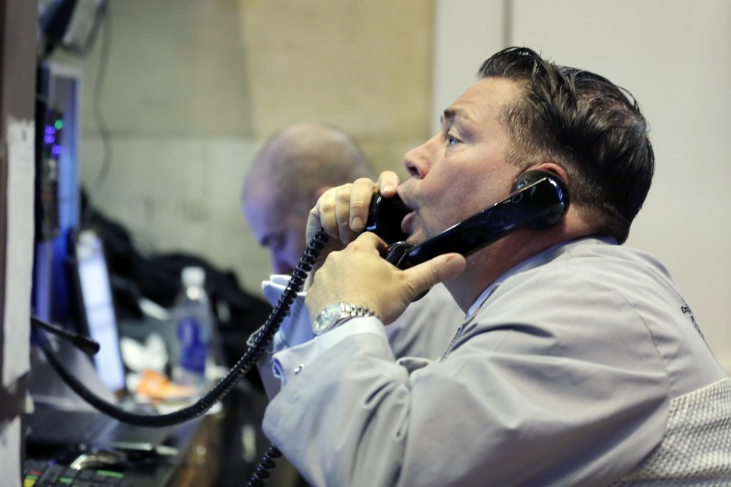 A trader works in his post on the floor of the New York Stock Exchange on Friday (AP Photo/Richard Drew)
