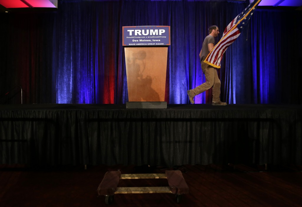 A worker clears off the stage after Donald Trump spoke at his caucus night rally, on Monday night, in West Des Moines, Iowa. (AP Photo/Jae C. Hong)