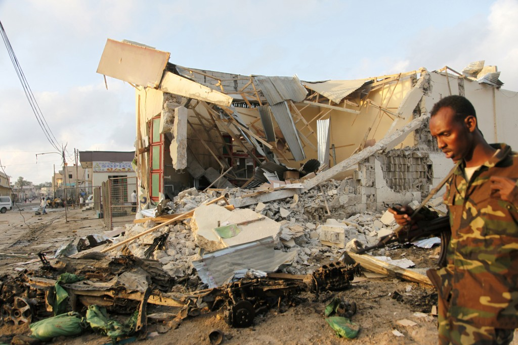 A Somali soldier walks near destroyed buildings, Saturday, Feb. 27, 2016 after a suicide car bomb on Friday night in Mogadishu, Somalia. A suicide bomber rammed his car into the SYL hotel's entrance in Mogadishu and blew it up, allowing gunmen to fight their way past hotel guards at the first security barrier, said Capt. Mohamed Hussein. (AP Photo/Farah Abdi Warsameh)