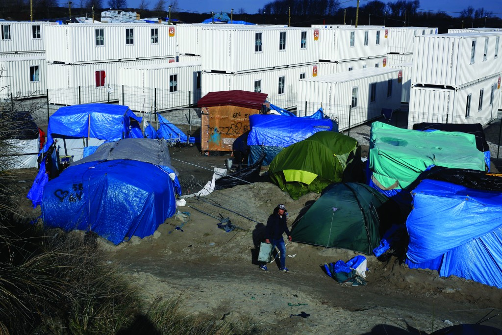 A migrant walks in a makeshift camp outside Calais, France, Tuesday. (AP Photo/Jerome Delay)