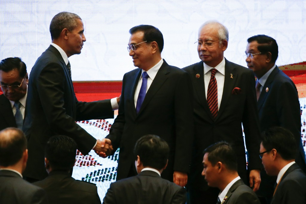 FILE - In this Nov. 22, 2015 file photo, U.S. President Barack Obama, left, shakes hands with Chinese Premier Li Keqiang, second left, while Malaysian Prime Minister Najib Razak, second right, and Laotian Prime Minister Thongsing Thammavong look on during the 10th East Asia Summit at the 27th ASEAN Summit in Kuala Lumpur, Malaysia. With the symbolic handshakes and unity photo-op, Obama's high-profile summit with Southeast Asian leaders in California this week aims to step up pressure against China's increasingly worrisome behavior in disputed waters. (AP Photo/Vincent Thian, File)