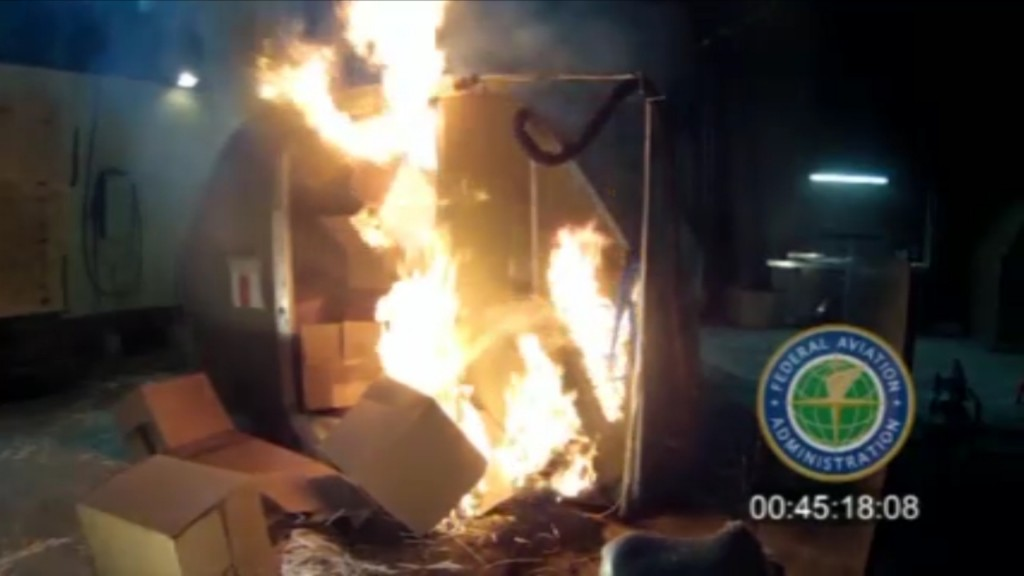 FILE - This file frame grab from video, provided by the Federal Aviation Administration (FAA) shows a test at the FAAs technical center in Atlantic City, N.J., in April 2014, where a cargo container was packed with 5,000 rechargeable lithium-ion batteries. A U.N. aviation agency has voted to ban cargo shipments of rechargeable lithium batteries on passenger planes because they can create intense fires capable of destroying the aircraft. The Feb. 22, 2016, decision by International Civil Aviation Organization's top-level governing council isn't binding, but most countries follow the agency's standards. The ban goes into effect on April 1.(AP Photo/FAA, File)