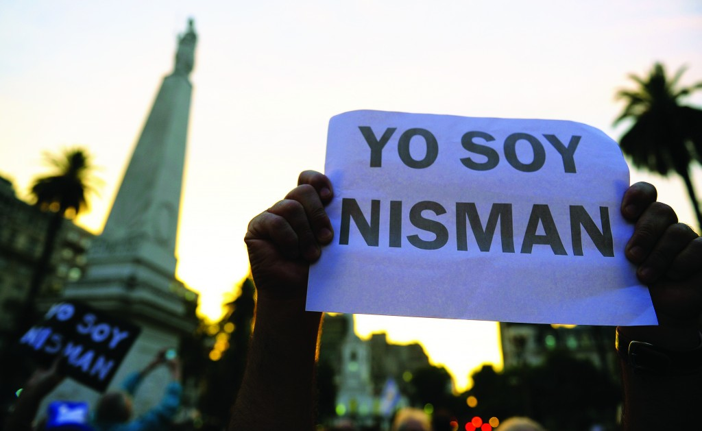 """A man holds a sign reading """"I am Nisman"""" during a demo at Mayo square, in Buenos Aires on January 19, 2015, against the death of Argentine public prosecutor Alberto Nisman, who was found shot dead earlier, just days after accusing President Cristina Kirchner of obstructing a probe into a 1994 Jewish center bombing. Nisman, 51, who was just hours away from testifying at a congressional hearing, was found dead overnight in his apartment in the trendy Puerto Madero neighbourhood of the capital. """"I can confirm that a 22-caliber handgun was found beside the body,"""" prosecutor Viviana Fein said. The nation's top security official said Nisman appears to have committed suicide. AFP PHOTO / ALEJANDRO PAGNI AFP PHOTO / ALEJANDRO PAGNI (Photo credit should read ALEJANDRO PAGNI/AFP/Getty Images)"""