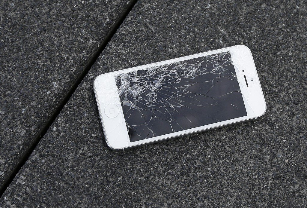 FILE - Apple iPhone with a cracked screen. (AP Photo/Ben Margot)