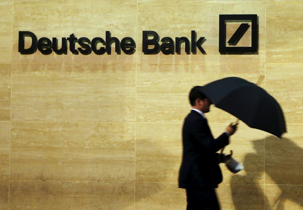 A man walks past Deutsche Bank offices in London in this December 5, 2013 file photo. REUTERS/Luke MacGregor/Files