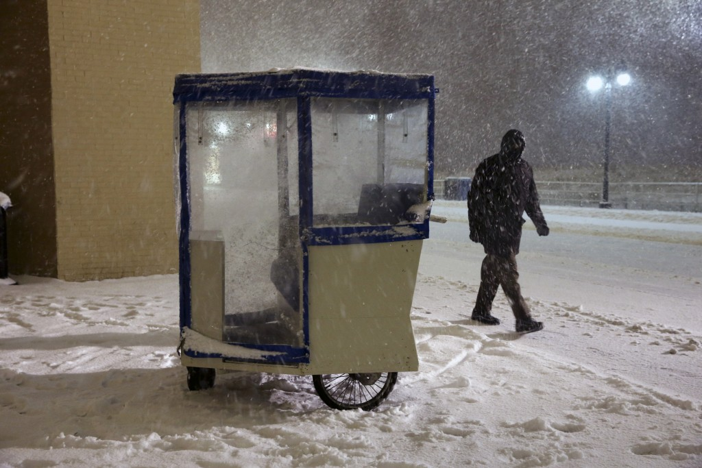 A man walks in blowing snow past a Push cart on the Boardwalk early Saturday, Jan. 23, 2016, in Atlantic City, N.J. Towns across the region are hunkering with the arrival of a major snowstorm. Most of the state was facing a blizzard warning from Friday evening until Sunday that called for up to 24 inches of snow, with the deepest accumulations in the central part of the state. (AP Photo/Mel Evans)