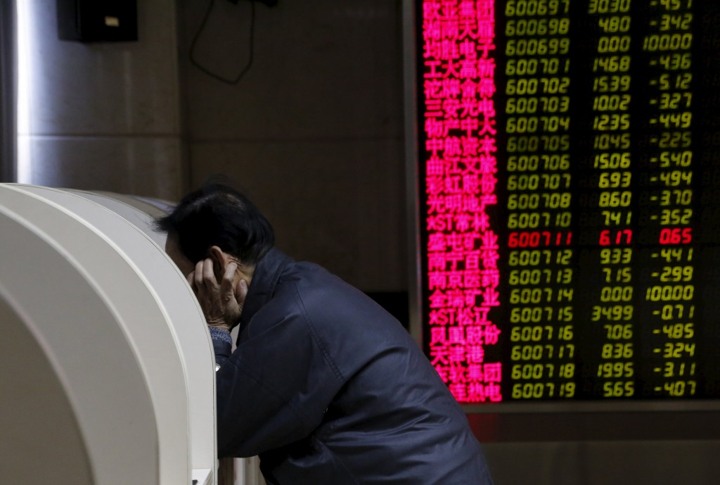 An investor uses a monitor to check stock information on desk in front of an electronic board showing stock information on the first trading day after the week-long Lunar New Year holiday at a brokerage house in Beijing, China, February 15, 2016. China stocks opened more than 2 percent lower on Monday, as they played catch-up with bearish global markets after the week-long Lunar New Year holiday.REUTERS/Kim Kyung-Hoon