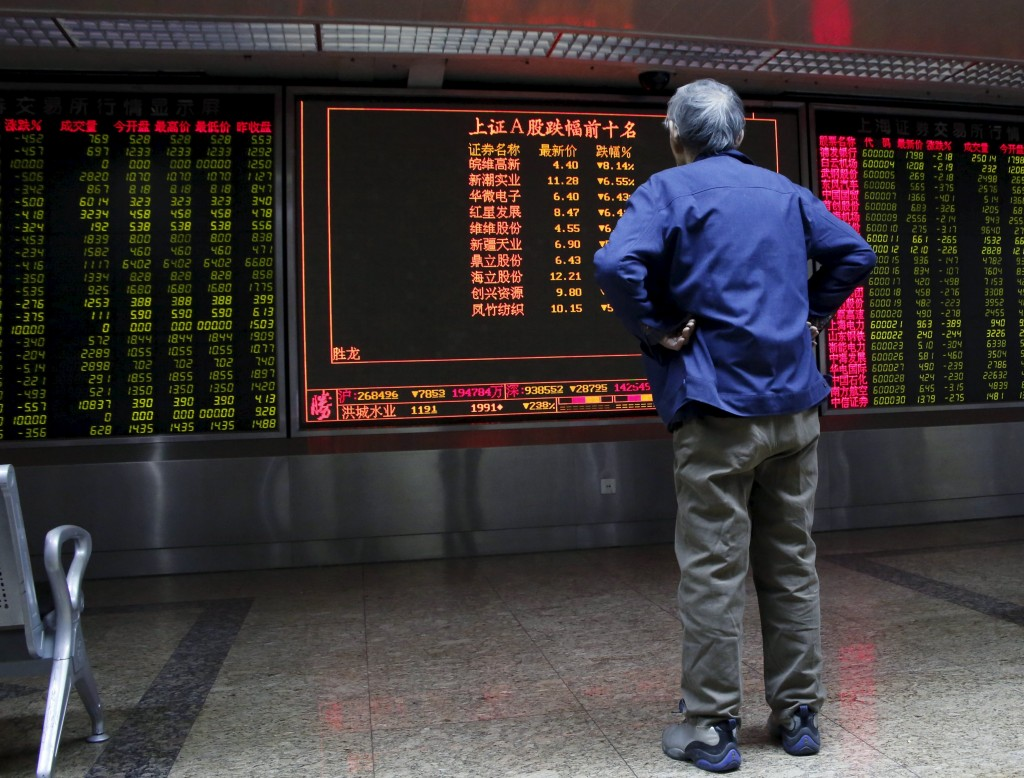 An investor watches an electronic board showing stock information on the first trading day after the week-long Lunar New Year holiday at a brokerage house in Beijing, China, February 15, 2016. China stocks opened more than 2 percent lower on Monday, as they played catch-up with bearish global markets after the week-long Lunar New Year holiday.REUTERS/Kim Kyung-Hoon