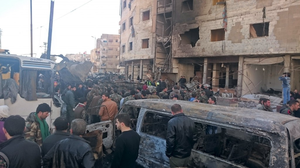 Residents and soldiers loyal to Syria's President Bashar al-Assad inspect damage after a suicide attack in Sayeda Zeinab, a district of southern Damascus, Syria January 31, 2016. At least 60 people were killed, including 25 Shi'ite fighters, and dozens wounded on Sunday by a car bomb and two suicide bombers in the district of Damascus where Syria's holiest Shi'ite shrine is located, a monitor said. Sunni fundamentalist Islamic State claimed responsibility for the attacks, according to Amaq, a news agency that supports the group. REUTERS/Stringer EDITORIAL USE ONLY. NO RESALES. NO ARCHIVE.