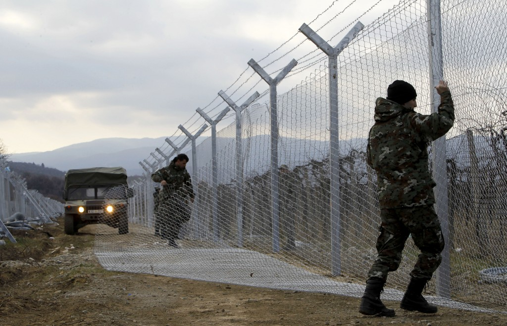 "FILE - In this February 8, 2016 file photo, Macedonian Army soldiers erect a second fence on the border line with Greece, near the southern Macedonia's town of Gevgelija. Six nations from Central and Eastern Europe meet Monday in Prague to discuss plans for a new ""line of defense"" for Europe that involves a double fence along Greece's northern border. (AP Photo/Boris Grdanoski, File)"
