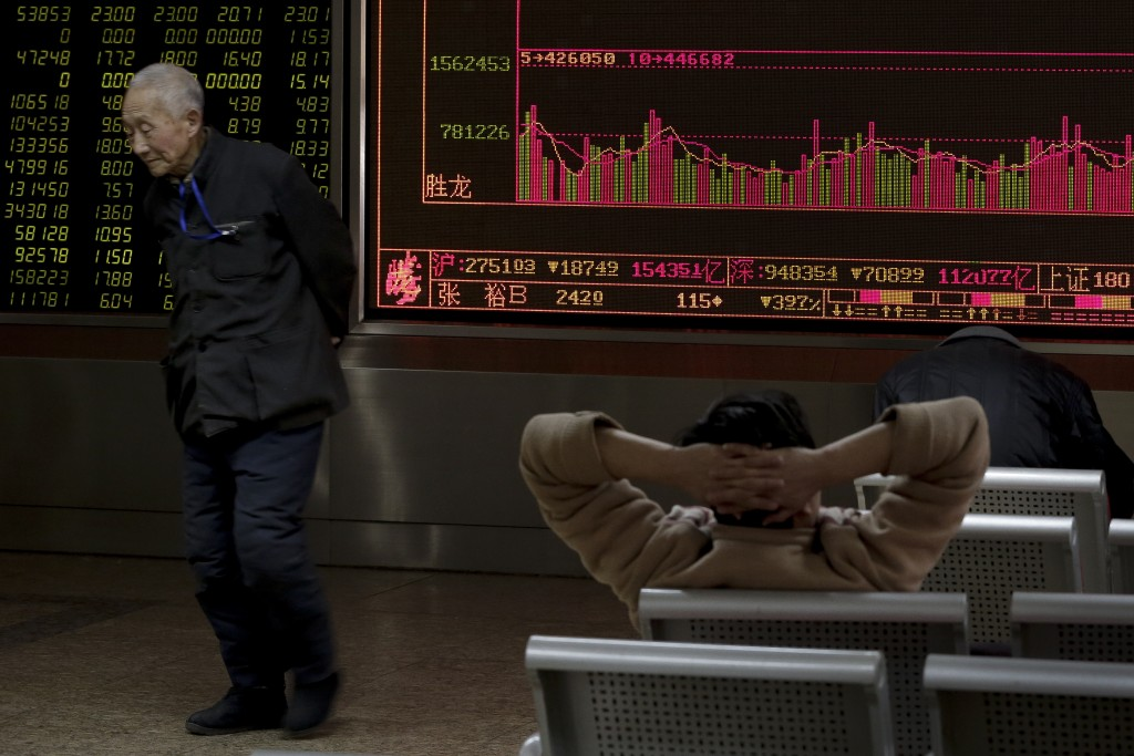 People looks at an electronic board displaying stock prices at a brokerage house in Beijing, Tuesday, Jan. 26, 2016. Asian stock markets sank Tuesday, led by a plunge in the Shanghai index, after a renewed slump in the price of oil kept investors on edge about the global economy. (AP Photo/Andy Wong)