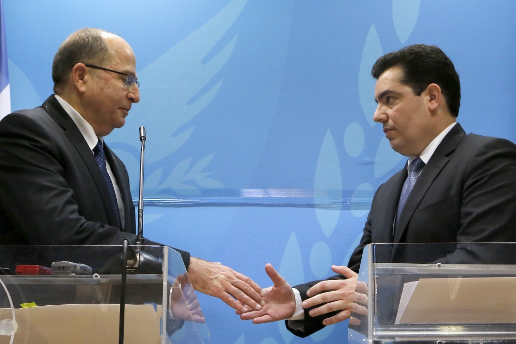 "Israeli Defense minister Moshe Yaalon, left, and his Cypriot counterpart Fotis Fotiou shake hands during their statements to the media after their meeting at the Defense ministry in capital Nicosia, Cyprus, Wednesday, Feb. 24, 2016. Israel's defense minister is accusing Iran of building an international terror network that includes 'sleeper cells' stockpiling arms, intelligence and operatives that are ready to strike on command in places including Europe and the U.S. Yaalon says Iran aims to destabilize the Middle East and other parts of the world and is training, funding and arming ""emissaries"" to spread revolution. He also says Tehran is the anchor of a ""dangerous axis"" that includes Baghdad, Damascus, Beirut, Saana and other cities in the region. (AP Photo/Petros Karadjias)"