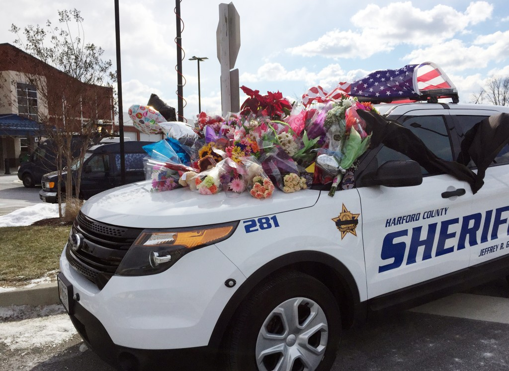 Tributes in memory of two slain deputies are stacked on a Harford County Sheriff's Office Department vehicle outside the department's southern precinct  in Edgewood, Md., on Thursday.  (AP Photo/Juliet Linderman)