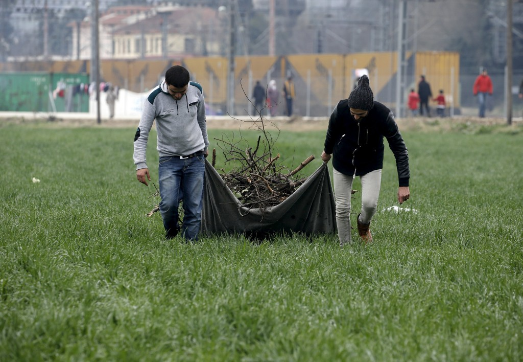 Refugees carry firewood on a field where migrants and refugees are camping by the Greek-Macedonian border February 28, 2016, as thousands of people wait to cross the border near the Greek village of Idomeni. REUTERS/Yannis Behrakis