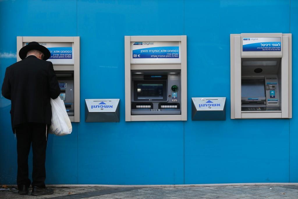 An ultra orthodox Jewish man cashes out money from an ATM machine in Jerusalem on July 15, 2015. Photo by Nati Shohat/Flash90 *** Local Caption *** çøãéí çøãé áð÷ ìàåîé ëñôåîè ëñó ëìëìä