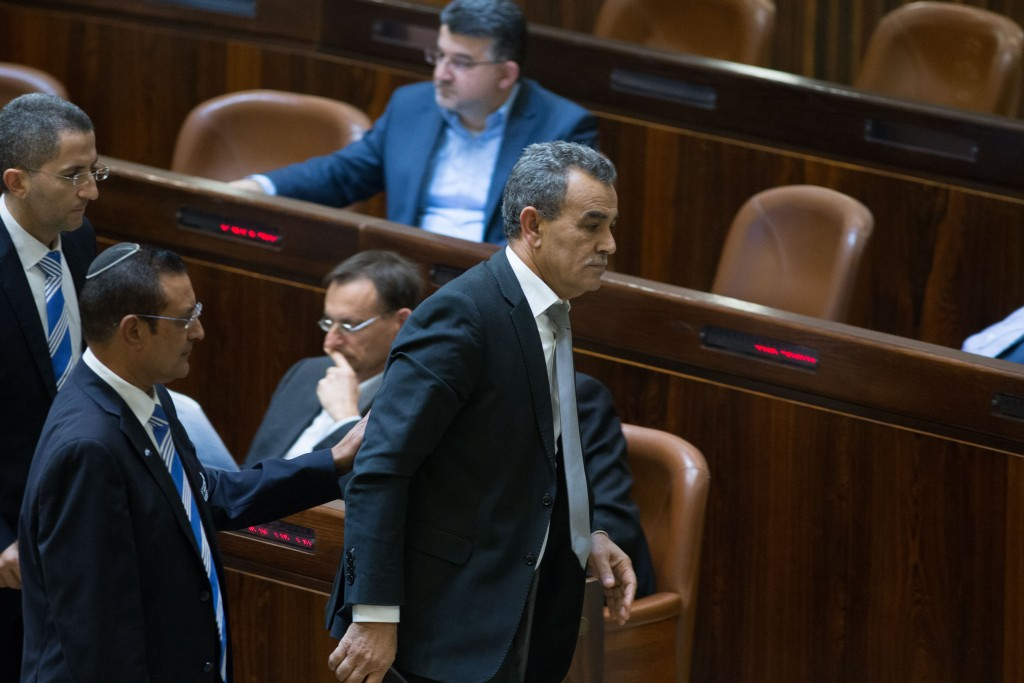 Joint Arab List member Jamal Zahalka is taken out of the Knesset after yelling during a plenum session on Monday. (Yonatan Sindel/Flash90)