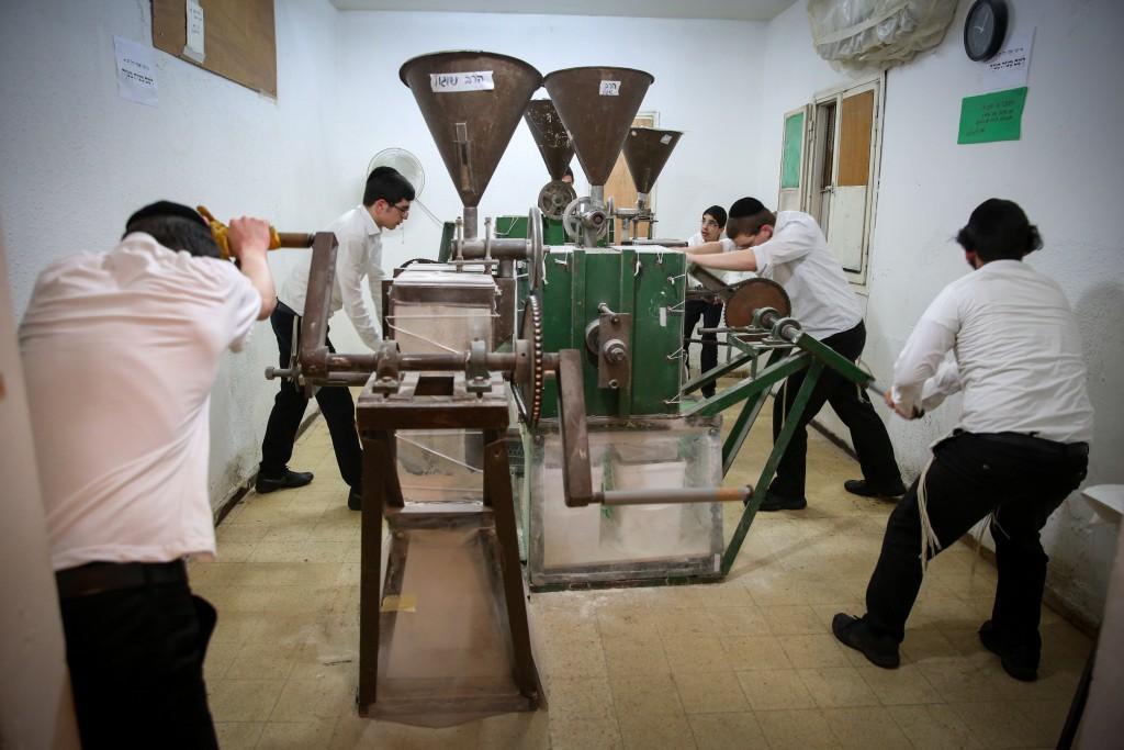 Bachurim grind flour for 'matzos', which will be eaten Pesach, in Bnei Brak. (Yaacov Cohen/Flash90)