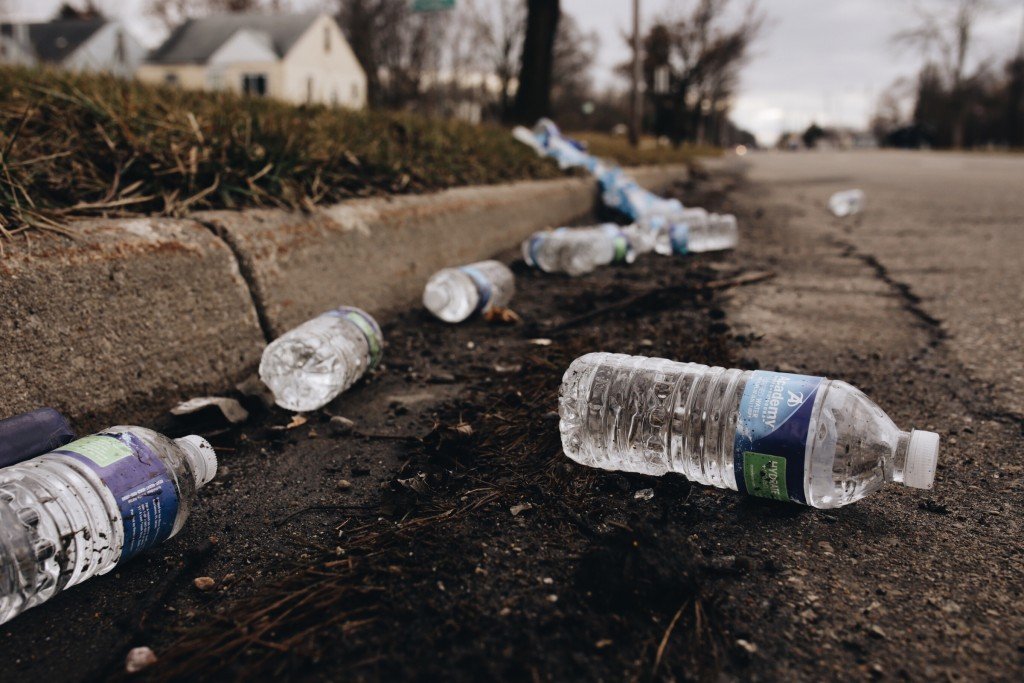 A broken case of water lays along the street near a water station in Flint, Mich., on Wednesday. (Ryan Garza/Detroit Free Press via AP)
