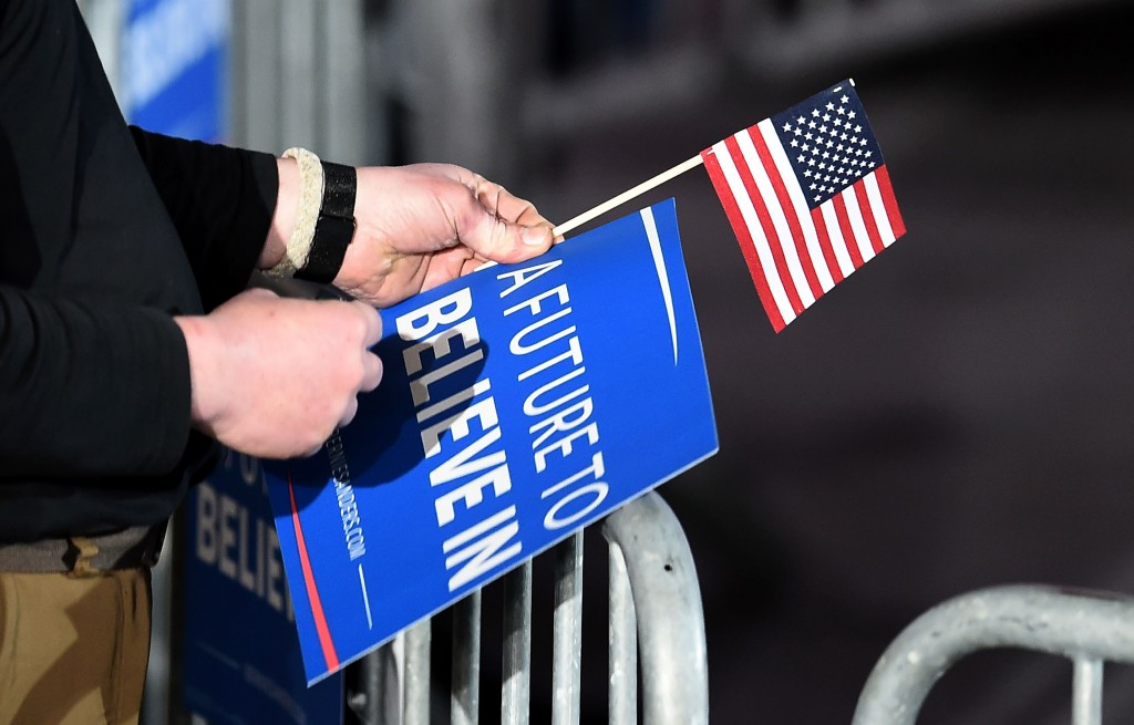 A supporter of US Democratic presidential candidate Bernie Sanders holds a campaign poster and a US flag as he arrives for primary night rally in Concord, New Hampshire, on February 9, 2016. (JEWEL SAMAD/AFP/Getty Images)