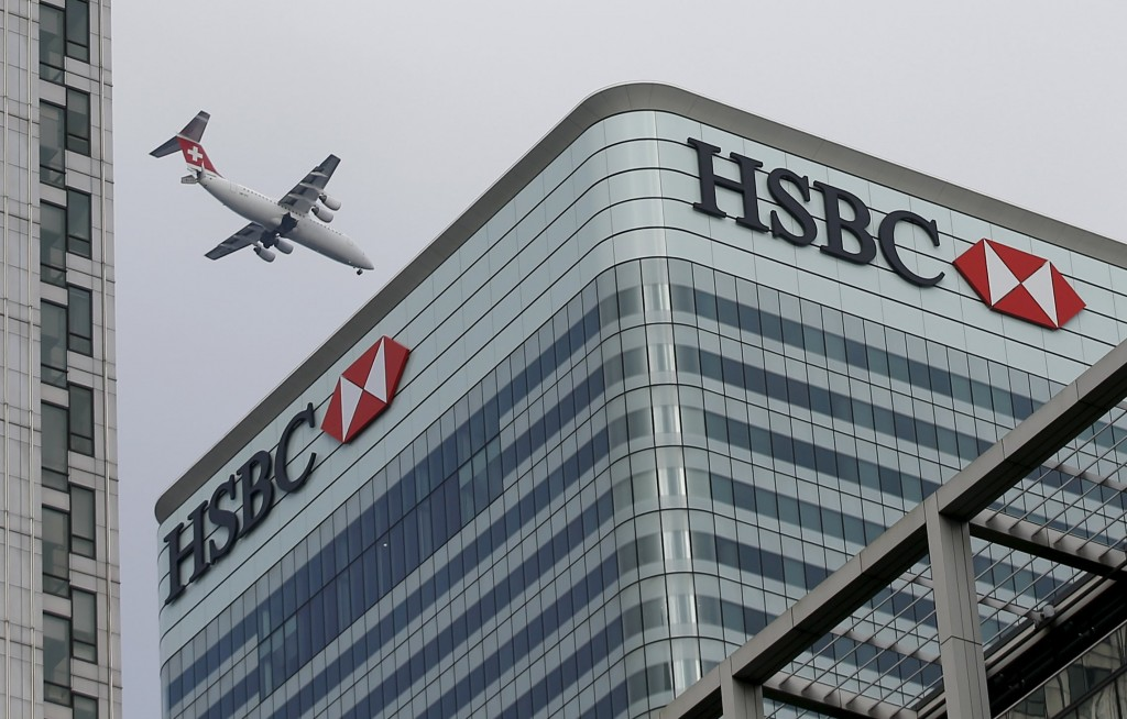 A Swiss International aircraft flies past the HSBC headquarters building in the Canary Wharf financial district in east London in this February 15, 2015 photo. HSBC Holdings decided on February 14, 2016 to keep its headquarters in Britain, rejecting the option of shifting its centre of gravity back to its main profit-generating centre Hong Kong after a 10 month review. REUTERS/Peter Nicholls/Files