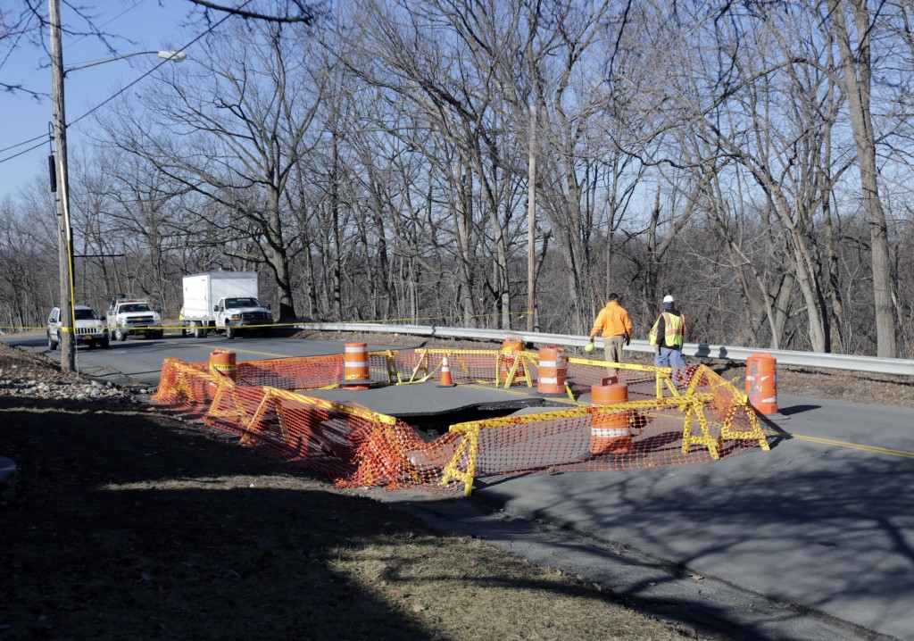 Barriers surround a sinkhole Monday in Troy, NY. (AP Photo/Mike Groll)