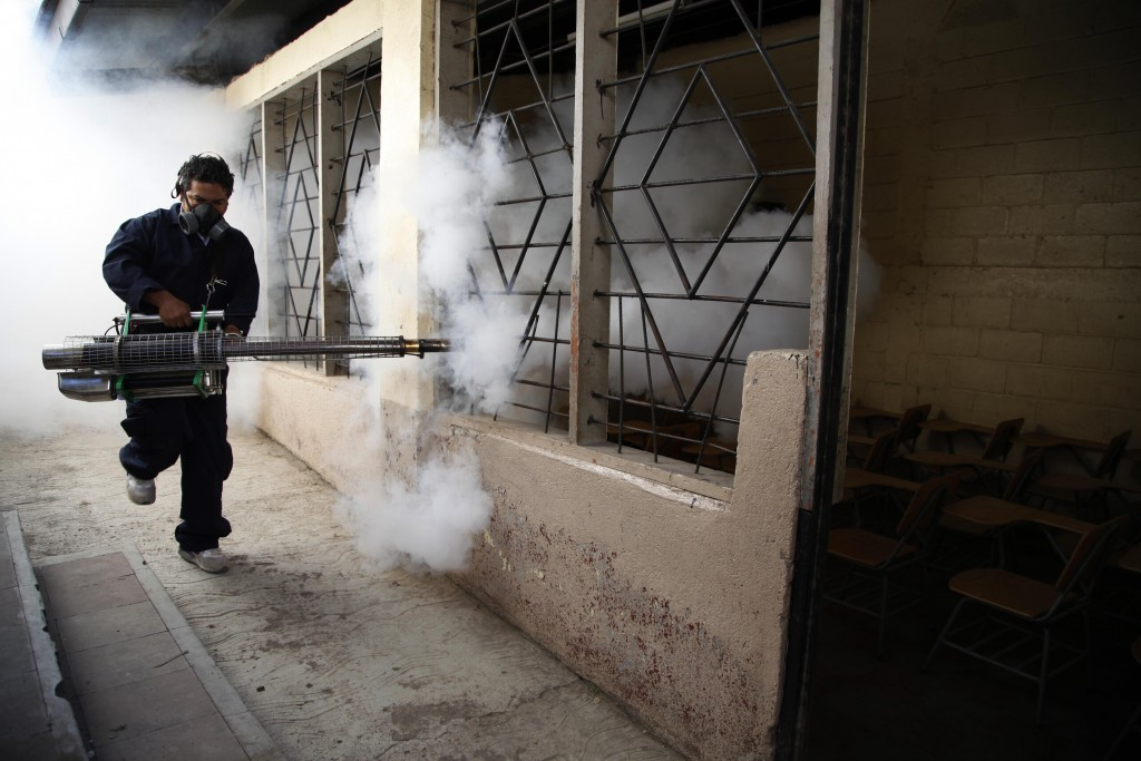 A city worker fumigates a public school to combat the Aedes aegypti mosquito, known to transmit dengue, Chikungunya and Zika, in Tegucigalpa, Honduras, Tuesday, Feb. 2, 2016. The World Health Organization has declared a global emergency over the explosive spread of the mosquito-borne Zika virus, which has been linked to birth defects in the Americas. Honduras is now reporting 3649 confirmed cases of Zika infections and has also declared a state of national emergency. (AP Photo/Fernando Antonio)