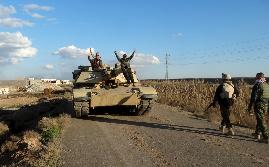 Iraqi security forces gesture from the top of a tank as they gather in Jweba on the eastern fringes of Ramadi, February 8, 2016. Iraqi forces recaptured territory from Islamic State militants on Tuesday which links the recently recaptured city of Ramadi to a major army base in western Iraq, the military said. A statement broadcast on state television said the army, police and counter-terrorism forces had retaken several areas including the town of Husaiba al-Sharqiya, about 10 km (6 miles) east of Ramadi. Picture taken February 8, 2016. REUTERS/Stringer FOR EDITORIAL USE ONLY. NO RESALES. NO ARCHIVE. TPX IMAGES OF THE DAY