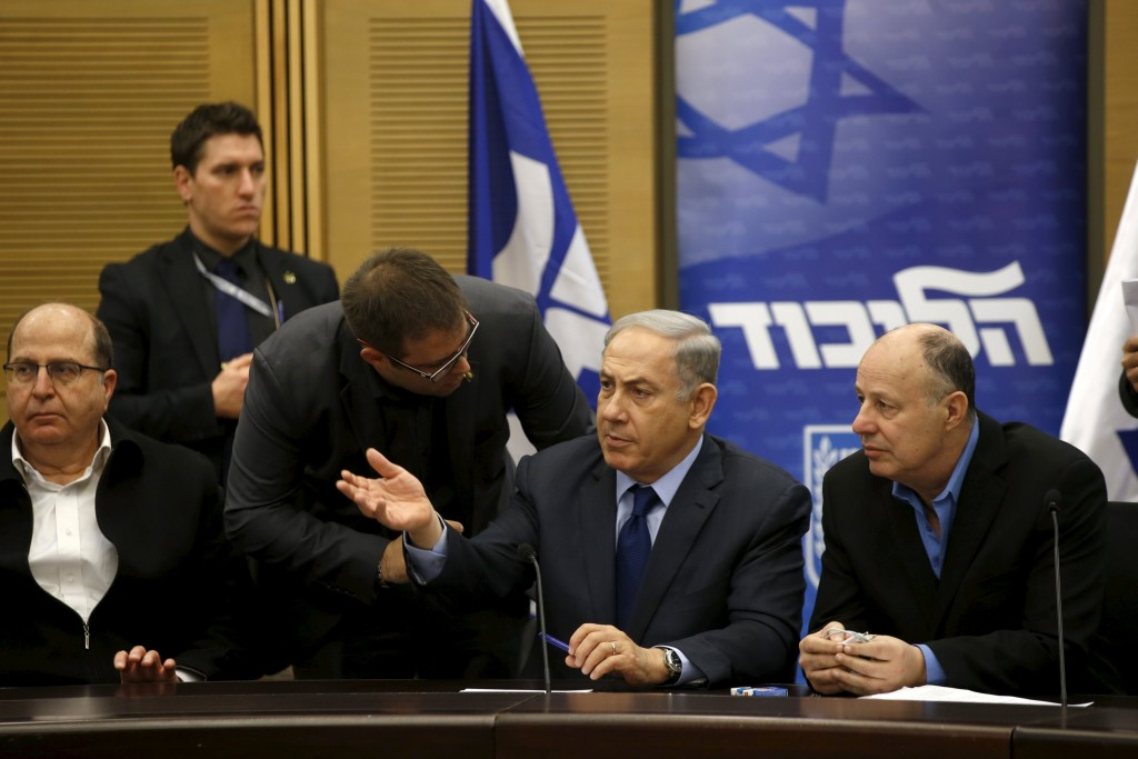 Israel's Prime Minister Benjamin Netanyahu (C) chats with members of his party during a meeting of his Likud party meeting in the Israeli parliament in Jerusalem February 8, 2016. A bill that opponents say targets Israeli human rights groups critical of Israel's policies towards the Palestinians was set to win initial approval in parliament on Monday with the support of the country's right-wing. It is widely expected to receive preliminary approval in the Knesset late on Monday. REUTERS/Ronen Zvulun