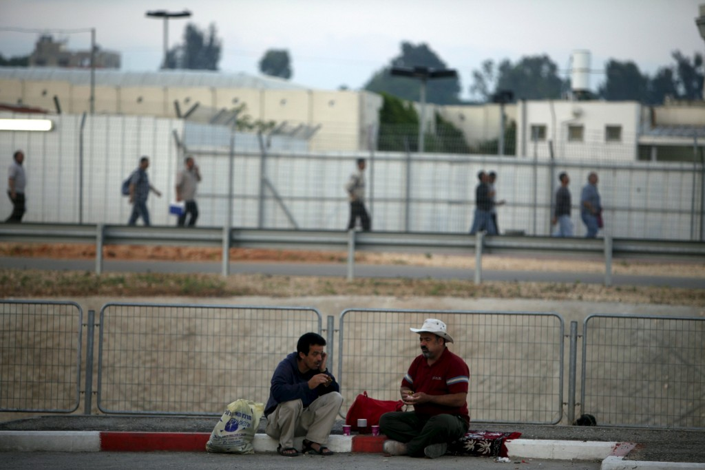Palestinian labourers wait for work on the side of a road after crossing through Israel's Eyal checkpoint (seen in the background) from the West Bank town of Qalqilya, in this June 1, 2011 file photo. Israel plans to increase the number of entry permits it grants to Palestinian workers, Palestinian and Israeli sources said on February 8, 2016, in a drive to ease economic hardship that has contributed to a wave of Palestinian attacks. REUTERS/Nir Elias/Files
