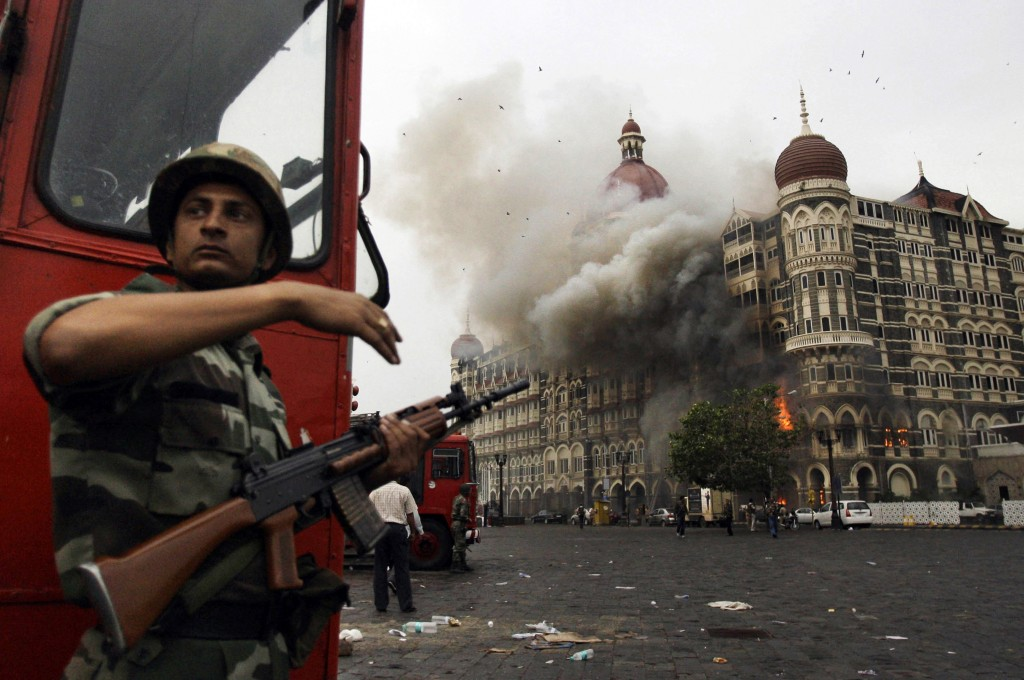 FILE- In this Nov. 29, 2008, file photo, an Indian soldier takes cover as the Taj Mahal hotel burns during gun battle between Indian military and militants inside the hotel in Mumbai, India. A Pakistani-American who helped plan a 2008 attack on India's financial hub has told a court in India that he traveled to India seven times to scout potential targets for a Pakistan-based group. (AP Photo/David Guttenfelder, File)