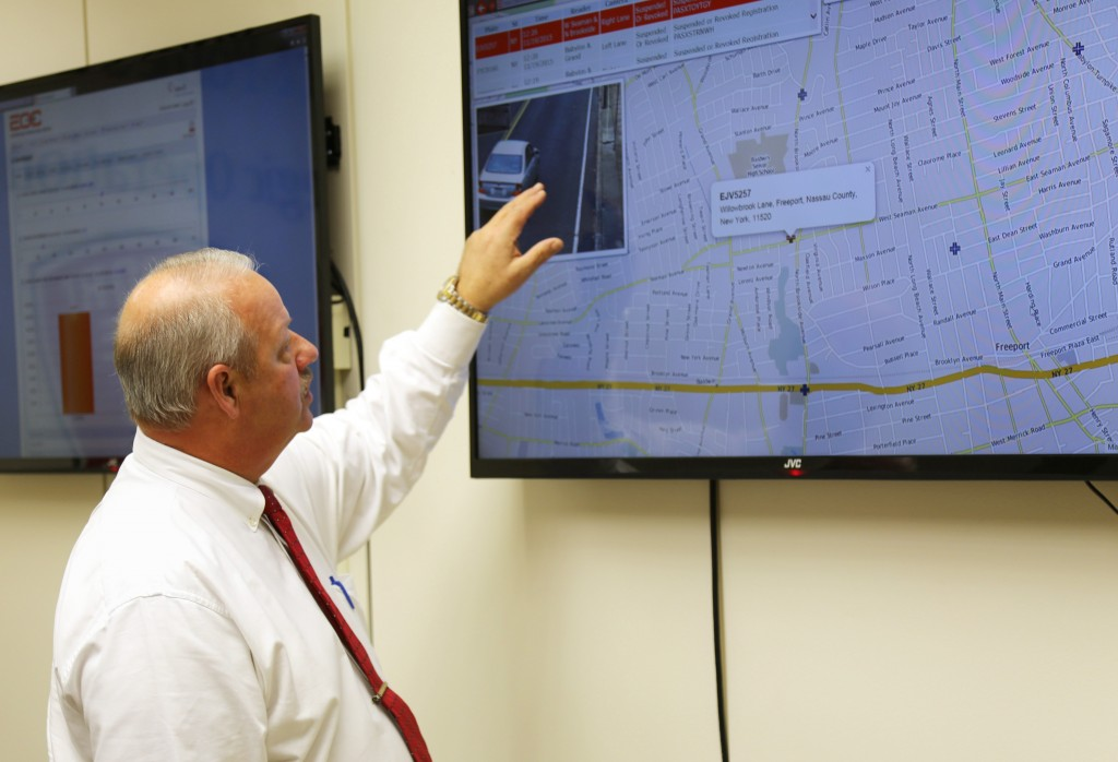 In this Nov. 19, 2015 photo, Freeport Mayor Robert Kennedy demonstrates the village's license plate scanner system at Village Hall in Freeport, N.Y. Since November 2015, the ring of 27 cameras has scanned more than 15.4 million license plates, resulting in 25 people being arrested, 500 cars being impounded and more than 2,000 summonses being issued.  (AP Photo/Michael Balsamo)