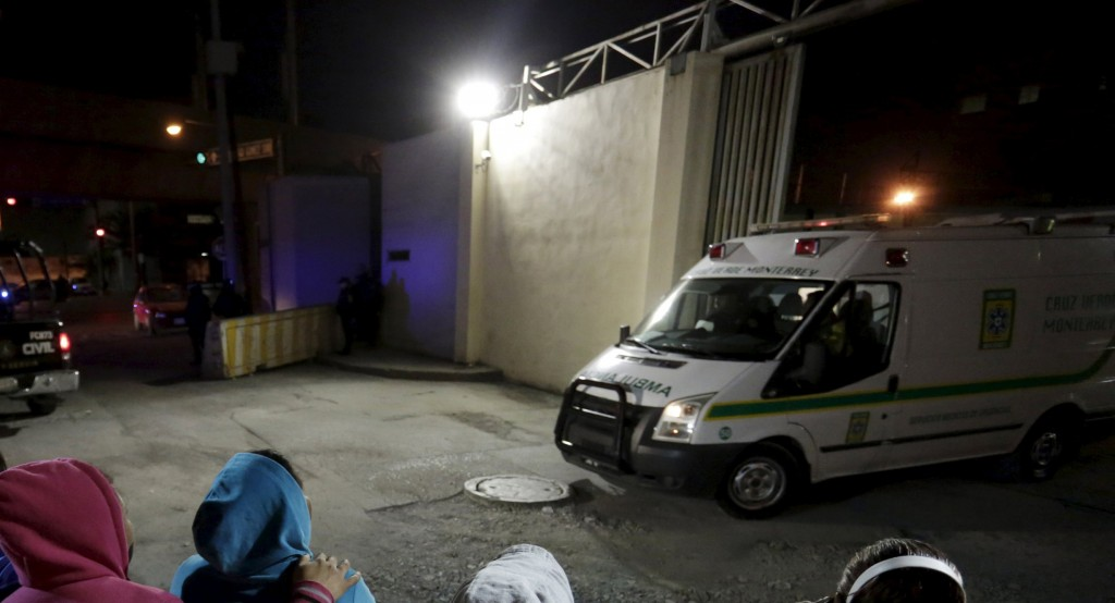 Family members of inmates stand outside Topo Chico Prison as an ambulance leaves the compound in Monterrey, Mexico, February 11, 2016. Dozens of people were killed in a riot in a prison in northeastern Mexico early on Thursday, local media reported, the just days ahead of a planned visit by Pope Francis to another prison near in Mexico's far north. REUTERS/Daniel Becerril