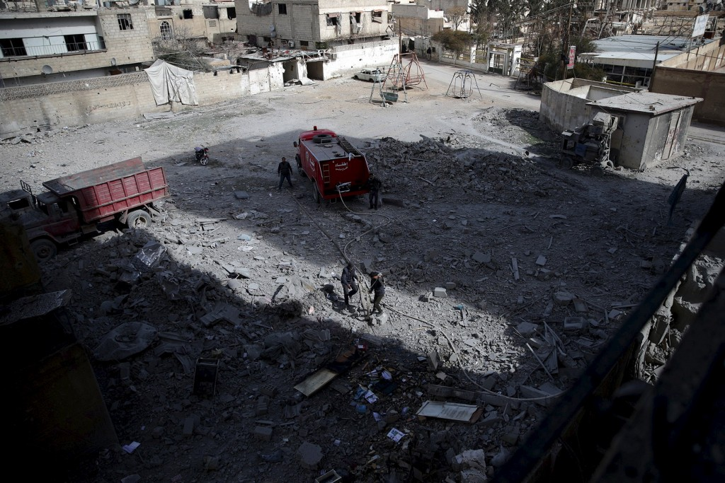 Civil defence members work at a site after airstrikes by pro-Syrian government forces in the rebel held Douma neighborhood of Damascus, Syria, February 14, 2016. REUTERS/Bassam Khabieh