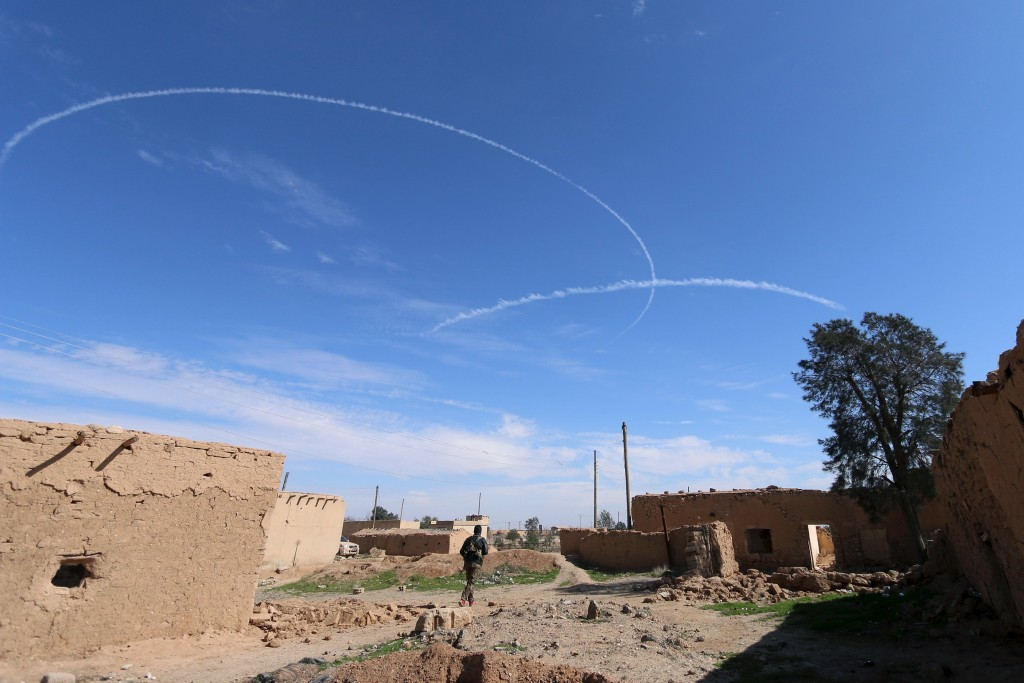 A Syria Democratic Forces fighter walks under contrails made by U.S. alliance air forces on the outskirts of al-Shadadi town, Hasaka countryside, Syria February 19, 2016. REUTERS/Rodi Said TPX IMAGES OF THE DAY