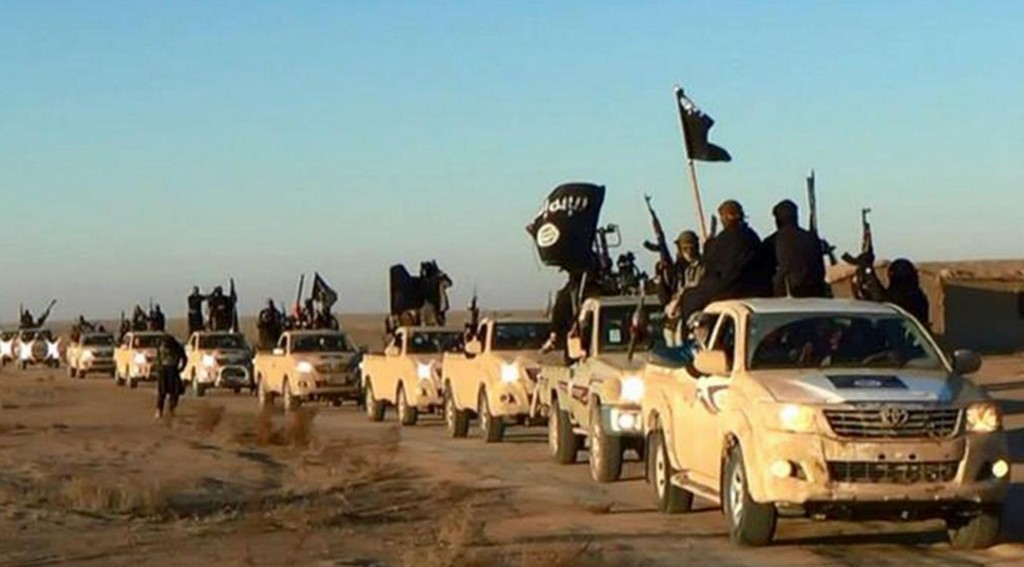"FILE - In this undated file photo released online in the summer of 2014 on a militant social media account, which has been verified and is consistent with other AP reporting, militants of the Islamic State group hold up their weapons and wave its flags on their vehicles in a convoy on a road leading to Iraq, in Raqqa, Syria. The extremist group that once bragged about minting its own currency is now accepting only U.S. dollars in Raqqa, slashing salaries across the board and imposing ""exit fees"" for those trying to leave its domain. (Militant photo via AP, File)"